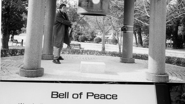 Man ringing large Bell of Peace inJ