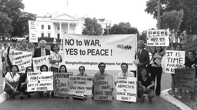 People holding signs for no war and peace in front of white house
